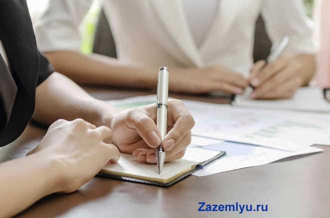Мужчина пишет в записной книжке, на заднем плане сидит девушка в белом пиджаке