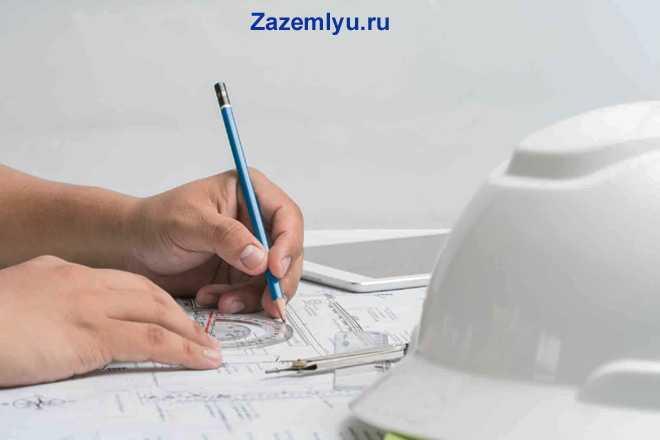 Мужчина делает чертеж, рядом лежит на столе белая строительная каска