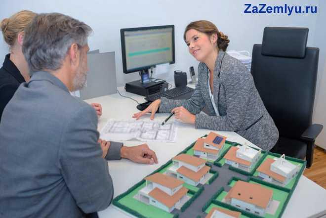 Женщина общается с клиентами, на столе стоит макет улицы с домами
