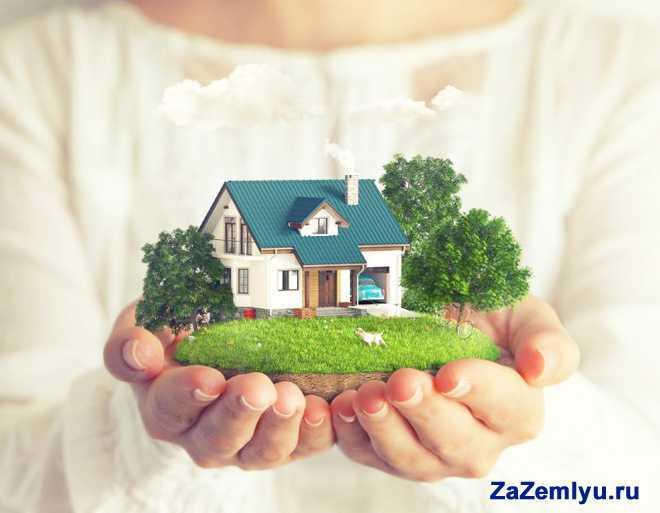 Девушка держит на ладонях дом с участком