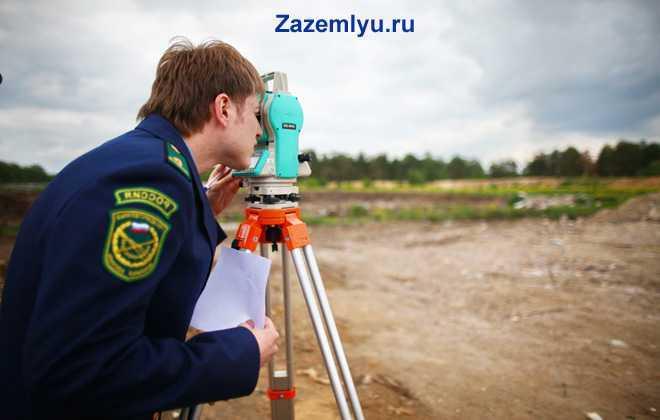 Мужчина в форме стоит в поле и смотрит в глазок нивелира