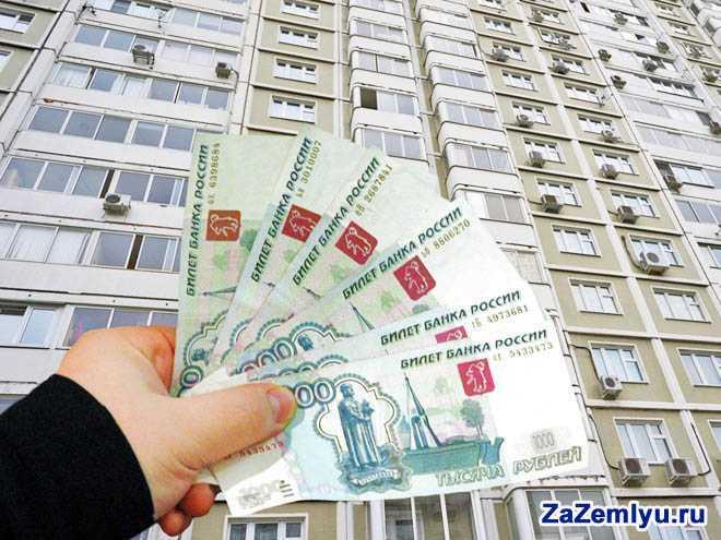 В руке мужчины тысячные купюры на фоне многоэтажного дома