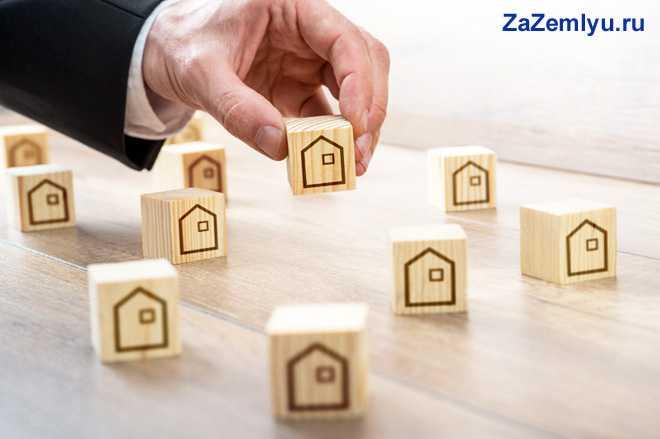 Мужчина выкладывает деревянные кубики, на которых нарисован домик