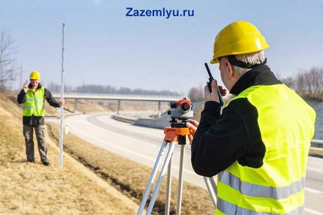 Рабочие  в строительных касках измеряют расстояние