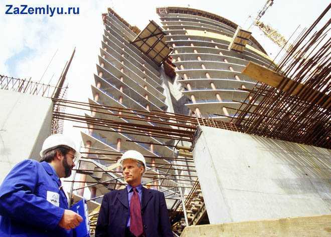 Рабочий и начальник общаются на фоне многоэтажного дома