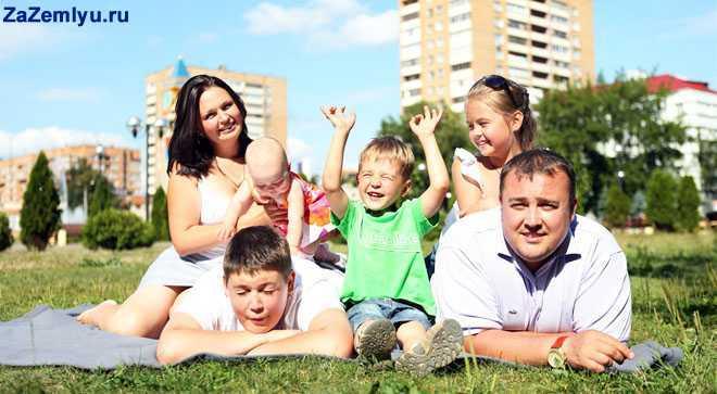 Счтасливая семья с детьми в городском парке