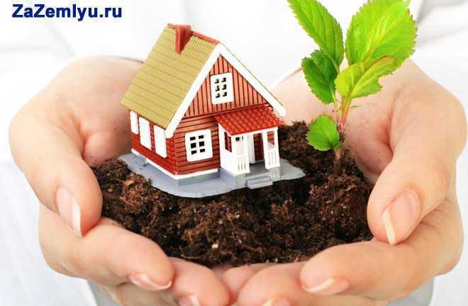 В руках человека дом с земельным участком