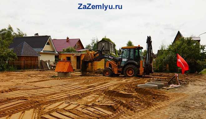 Трактор равняет строительный песок