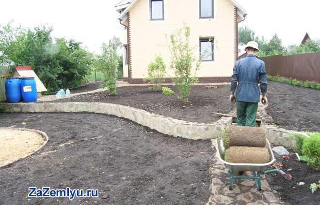 Рабочий создает ландшафтный дизайн двора дома