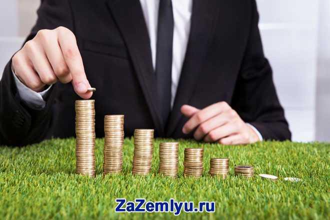 Бизнесмен выкладывает на травке золотые монеты в пирамидки