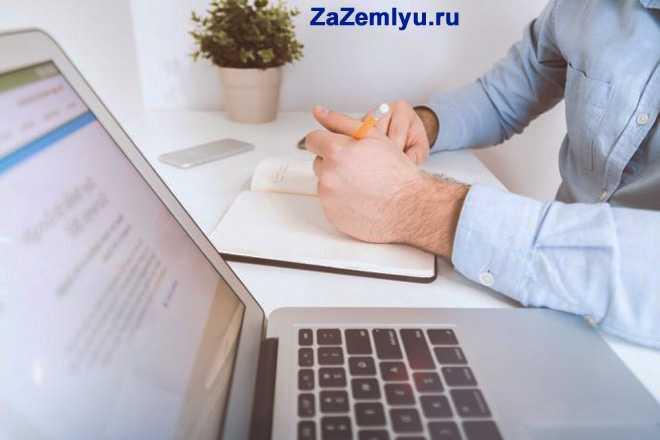 Мужчина делает записи в книжке, рядом стоит ноутбук