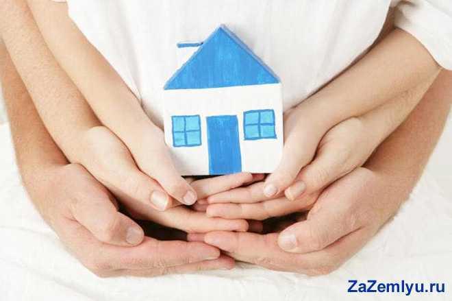 Семья держит в руках бумажный домик