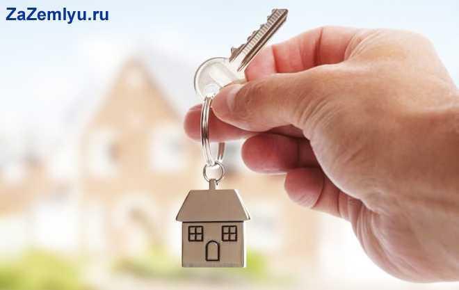 Человек держит в руке ключ от дома