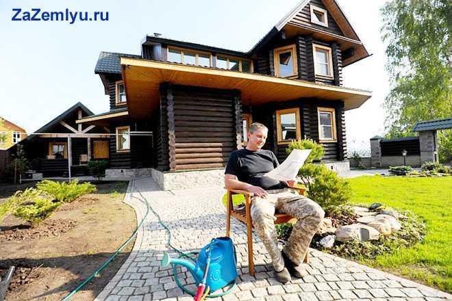 Мужчина сидит во дворе своего дома, читает документы
