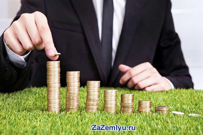 Бизнесмен складывает золотые монетки в пирамидки на зеленой траве