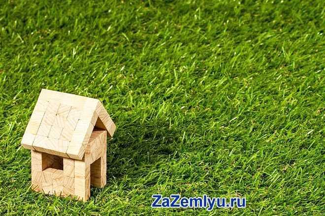 Домик из деревянных кубиков стоит на зеленой лужайке