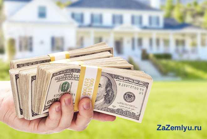 Мужчина держит в руке пачку денег на фоне дома