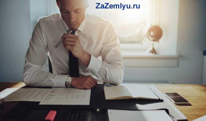 Офисный работник подписывает документы за своим рабочим местом