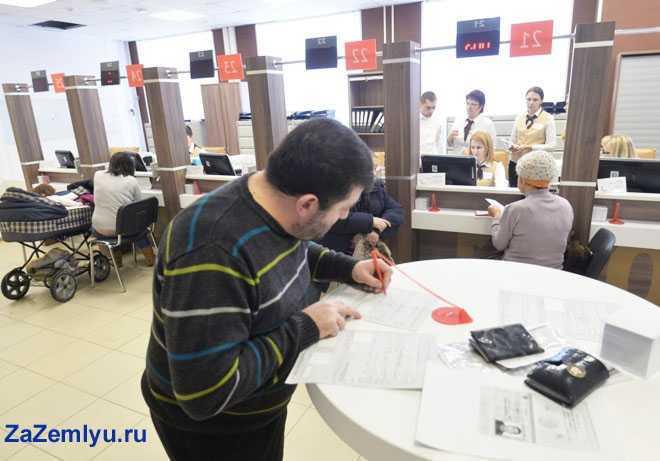 Мужчина подписывает документы в МФЦ