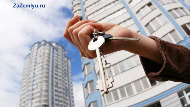 Мужчина держит в руке связку ключей на фоне дома
