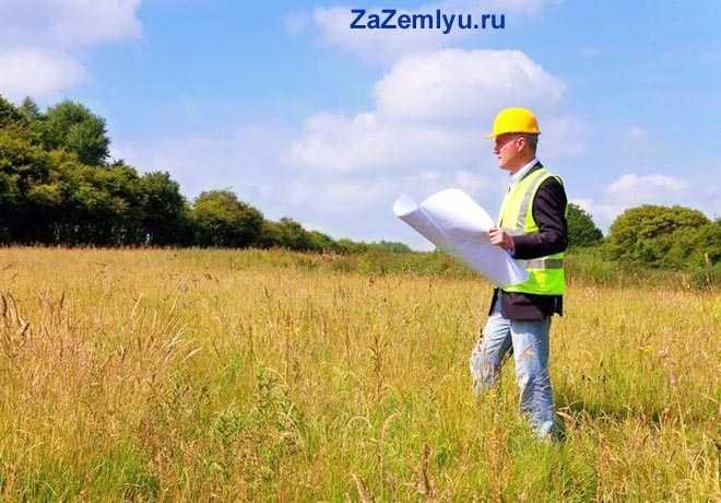 Строитель стоит с картой в поле