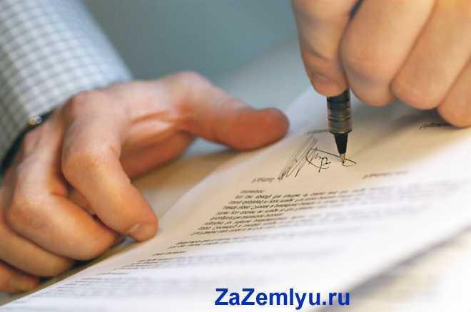 Мужчина ставит свою подпись в документах