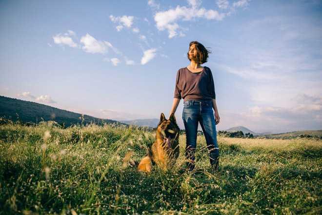Девушка гуляет с овчаркой на природе
