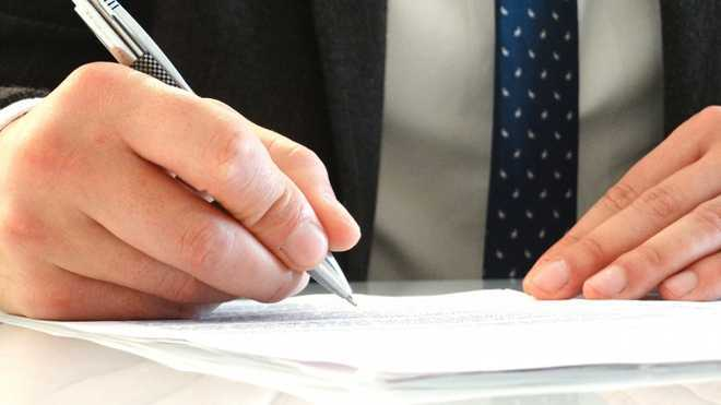 Мужчина ставит подпись в документах