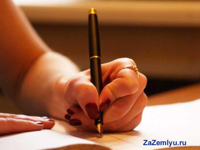 Девушка подписывает ручкой документы