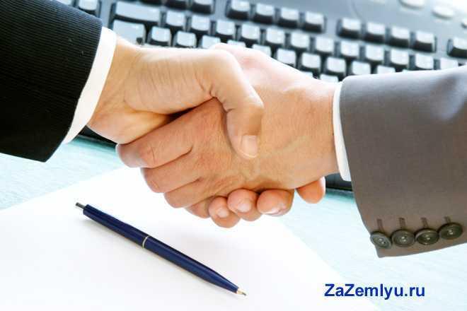 Бизнес-партнеры жмут друг другу руки на фоне компьютера