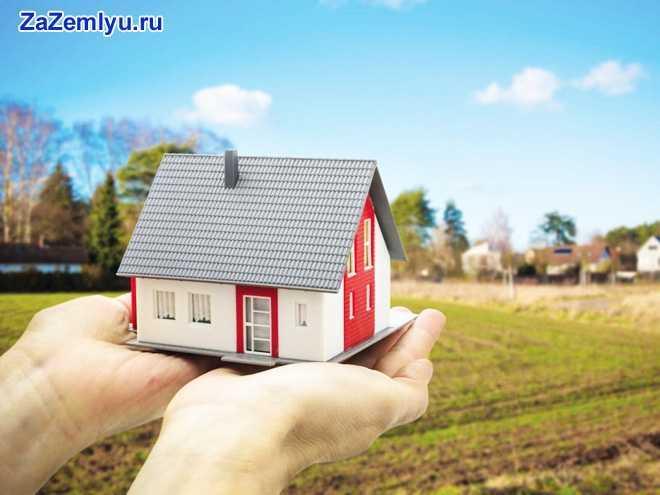 Человек держит в руках перед собой домик на фоне природы