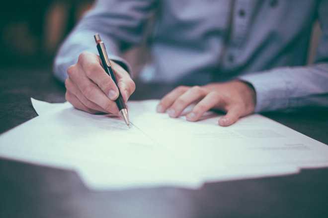 Мужчина подписывает документацию за столом