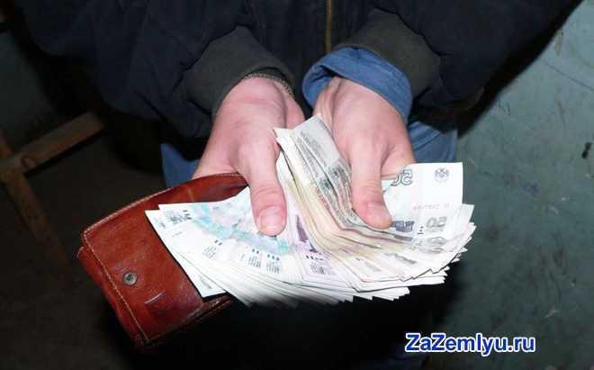 Мужчина держит в руках кошелек и деньги
