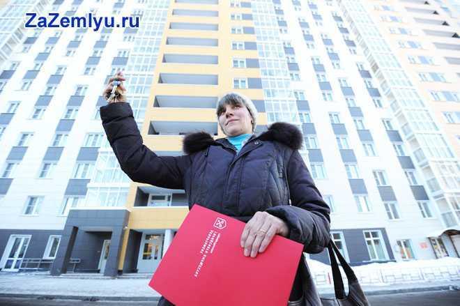 Девушка стоит с красной папкой и ключами на фоне многоэтажного дома
