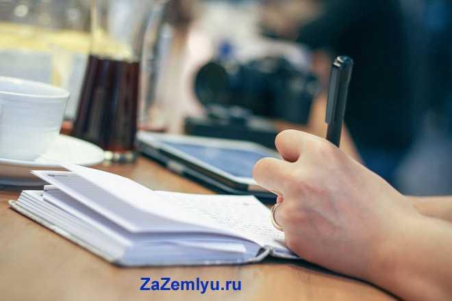 Мужчина делает записи в записной книге