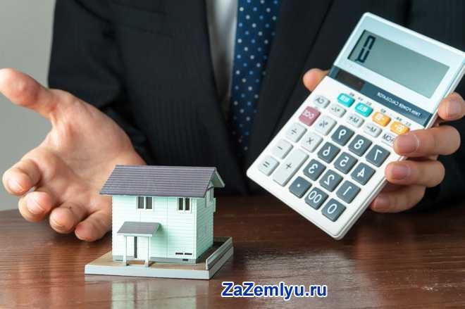 Бизнесмен держит в руке калькулятор, рядом стоит макет дома