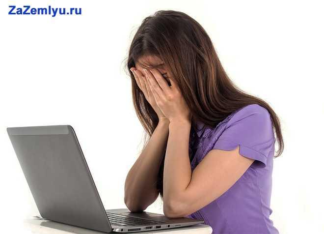 Девушка закрыла руками лицо и сидит за ноутбуком