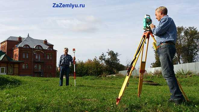 Рабочие измеряют границы участка
