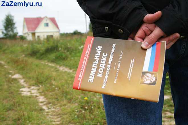 Мужчина держит в руке земельный кодекс и смотрит на дачный домик