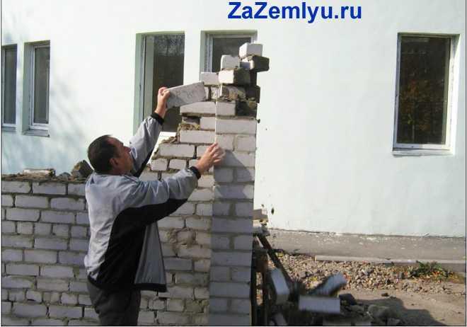 Мужчина делает постройку из кирпича