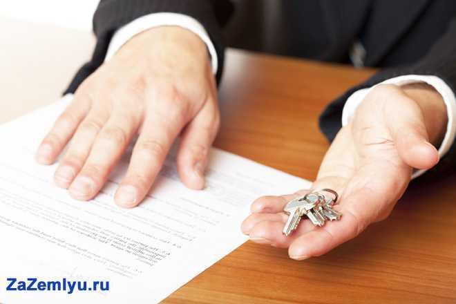Мужчина сидит за столом, в руке держит ключи и документы на квартиру