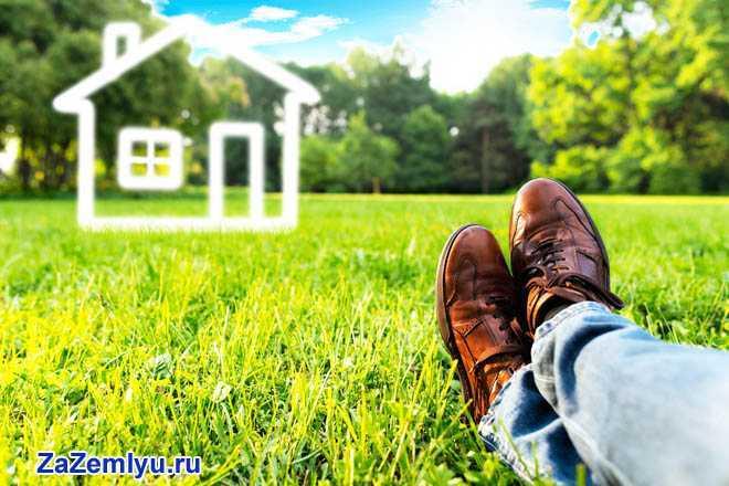 Мужчина лежит на травке и представляет дом