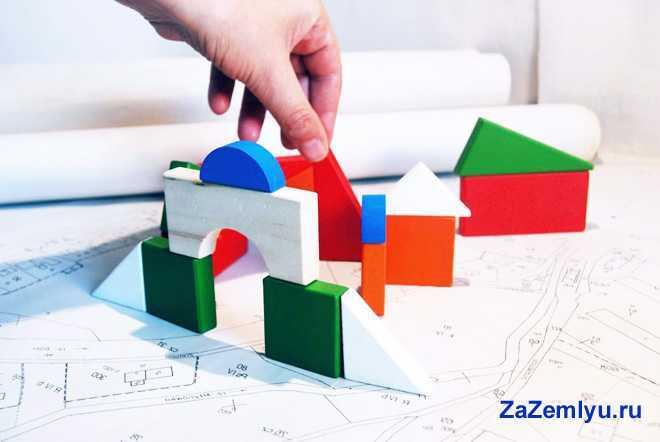 Человек строит домик из игрушечных блоков