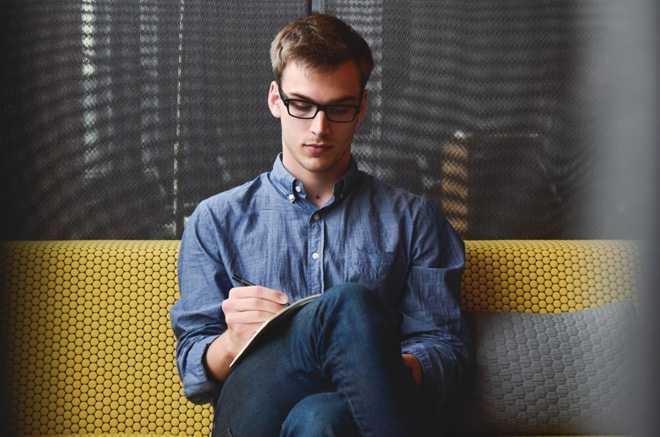 Молодой мужчина делает записи в тетрадь, сидит на диване