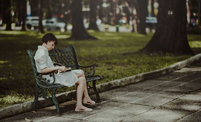 Девушка сидит на скамейке в парке