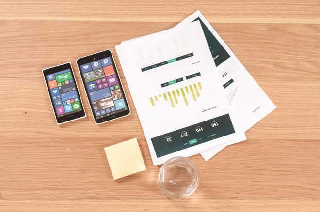 На письменном столе лежат документы, телефоны