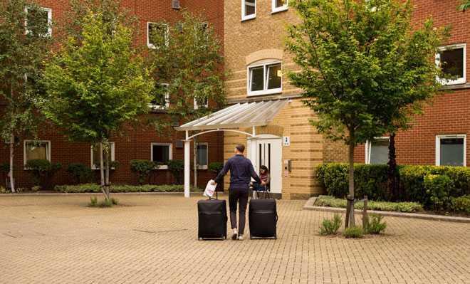 Мужчина с чемоданами подходит к зданию