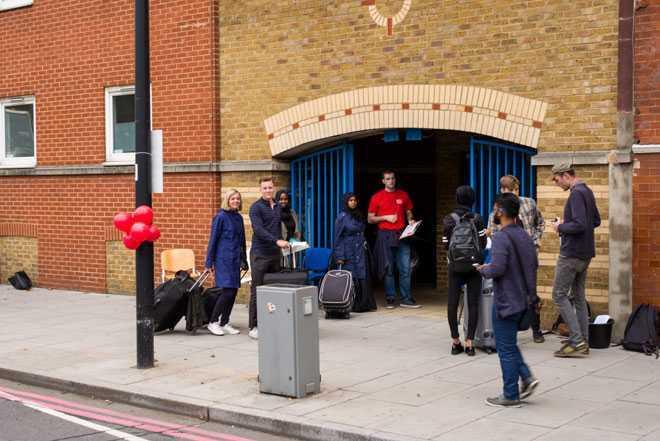 Люди с чемоданами стоят рядом с входом в здание