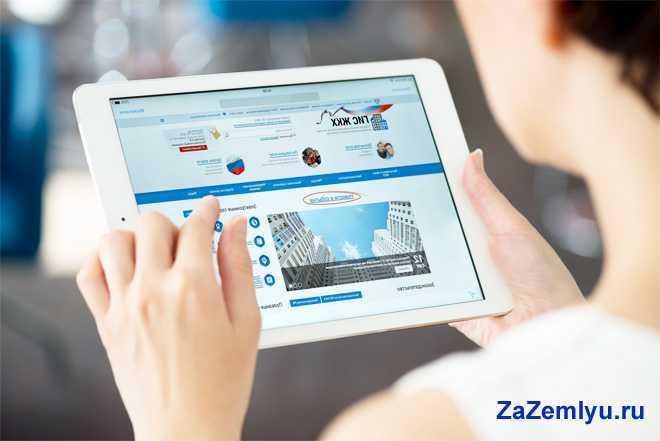 Девушка смотрит на планшете сайт управляющей компании