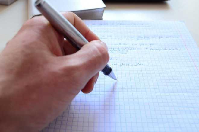 Мужчина пишет шариковой ручкой на листке бумаги